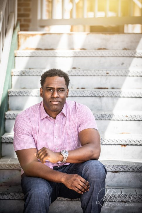 Head shots of black adult male on rusty staircase in northern Virginia with beautiful lighting.