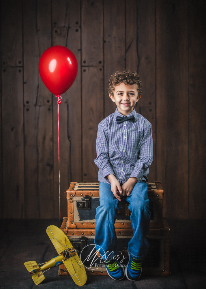 Birthday boy portraits with red balloon and teddy bear