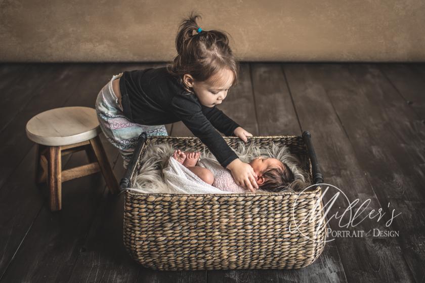 Portrait of Newborn with Big Sister in Wicker Basket